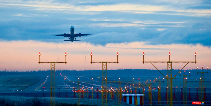 plane taking off from Helsinki Airport at sunset
